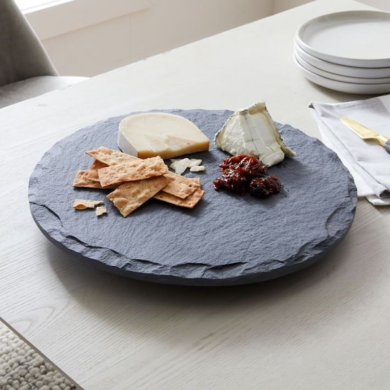 Our favorite boards for charcuterie boards: This slate lazy susan board at West Elm is affordable, and right-sized for appetizers for dinner